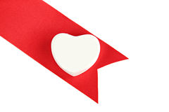 Red ribbon and white heart isolated. Royalty Free Stock Photo