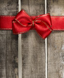 Red ribbon on wooden background. Red ribbon on old wooden background Royalty Free Stock Image
