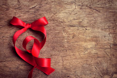 Red ribbon on wooden table Royalty Free Stock Photography