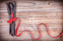 Red ribbon wraped around vanilla pods Royalty Free Stock Photo