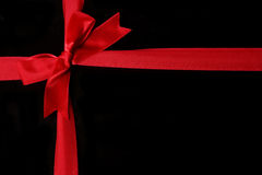 Red ribbon for your gift. The bow of red ribbon on black background Royalty Free Stock Image