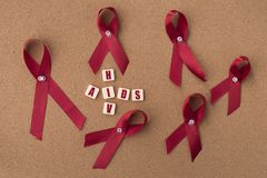 Red ribbons aids ribbon with AIDS/HIV word on notice board. Aids / HIV Concept. healthcare and medical concept stock photo
