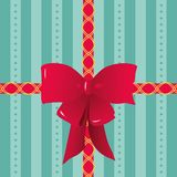 Red Ribbons and Bow Tied on Striped Gift Wrapping Paper. Illustration of a pretty red bow and two ribbons with golden decorations placed over a sea-green striped Royalty Free Stock Image