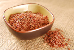 Red rice in bowl on hessian Stock Photography