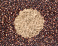Red rice on burlap fabric Stock Photo