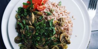 Red rice with mushrooms and tomatoes. Vegan dish. Stock Photo