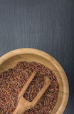Red rice and olive wood scoop in a wooden bowl on black background of slate or stone Stock Photo