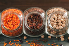 Red rice, red lentils and chickpeas in glass jars on a wooden table Royalty Free Stock Photos