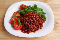 Red rice with tomatoes and green beans Stock Photos