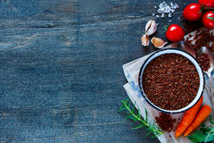Red rice and vegetables. Red rice and raw fresh vegetables ingredients for tasty cooking on rustic wooden background, top view.  Healthy eating or vegetarian Stock Images