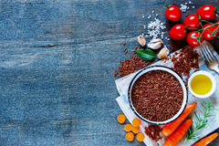 Red rice and vegetables. Raw red rice and fresh vegetables ingredients for tasty cooking on rustic wooden background, top view.  Healthy eating or vegetarian Stock Photo