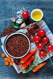 Red rice and vegetables. Top view of raw red rice and fresh vegetables ingredients for tasty cooking on rustic wooden background.  Healthy eating or vegetarian Royalty Free Stock Photos