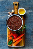 Red rice and vegetables. Wooden cutting board with raw red rice and fresh vegetables ingredients for tasty cooking over dark rustic background, top view Royalty Free Stock Image