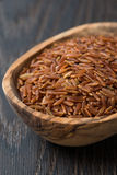 Red rice in a wooden bowl on a dark background Stock Images