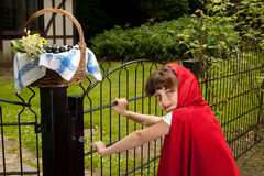 Red riding hood at gate. Little red riding hood arriving at the gate of her grandmother's cottage royalty free stock image