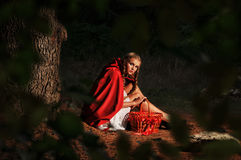 Red riding hood. Sits in a clearing in the forest Royalty Free Stock Photo