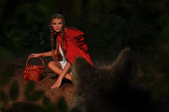 Red riding hood. Sits in a clearing in the woods. Wolf sneaks Stock Photography