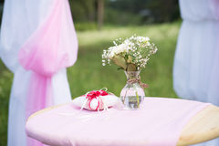 Red rings cushion on table with flowers. Wedding Royalty Free Stock Photos