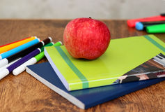 Red ripe apple close-up on school notebooks and some are multi-colored markers  pens  the wooden background Royalty Free Stock Photos