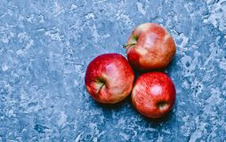 Red ripe apples on a concrete table. Fresh fruits. Loft and rust stock images