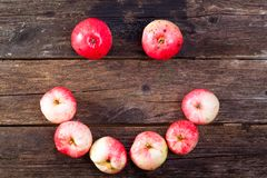 Red ripe apples. Smile made of red ripe apples on the vintage wooden table royalty free stock photo