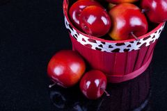 Red apples in a red basket. Red ripe apples in valentine`s red basket on a black background royalty free stock photo