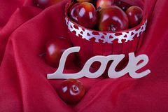 Red apples in a red basket. Red ripe apples in valentine`s red basket Love word on a red background, valentine`s concept stock photo