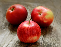 Red ripe apples on wooden surface Stock Photos