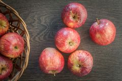 Red ripe Appples on a dark rustic wooden background, with a wooden basket. Top view stock photos