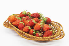 Red ripe berries of the strawberries on light background. Mature berries of the strawberry in braided plate are insulated on white background Royalty Free Stock Photo