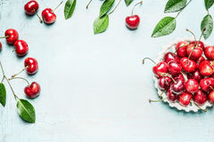 Red ripe cherries in bowl with twigs and leaves on light blue background, top view frame. Summer berries Royalty Free Stock Photography