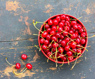 Red ripe cherries with tails in a circular plate on an old black wooden background with a crack Stock Photo