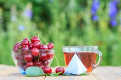 Red ripe cherry fruits with peduncles in glass bowl and cup of tea stock images