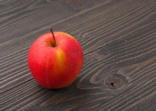 Red ripe juicy apple on a dark wooden background Royalty Free Stock Image