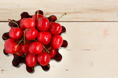 Red ripe juicy sweet cherry lies on vintage wooden background. Sweet summer berries. Royalty Free Stock Photography