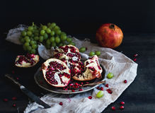 Red ripe peeled pomegranate on rustic metal plate and beige kitchen towel over dark background Stock Images