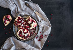 Red ripe peeled pomegranate on rustic metal plate and beige kitchen towel over dark background Stock Image