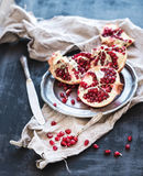 Red ripe peeled pomegranate on rustic metal plate and beige kitchen towel over dark background Stock Photo