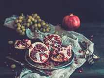 Red ripe peeled pomegranate on rustic metal plate Royalty Free Stock Image