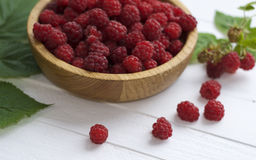 Red ripe raspberries on a white wooden table. And a bowl full of raspberries Stock Photography