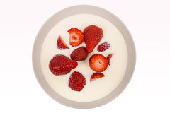 Red ripe strawberries in a bowl. With the cream and milk on a white background Royalty Free Stock Image