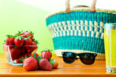Red ripe strawberry with shopping basket on the table Stock Photos
