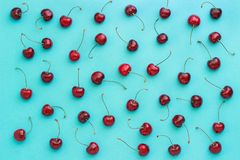 Red ripe sweet cherry on blue background, texture royalty free stock image