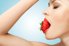 Red-ripe temptation. A portrait of a nude sexy woman holding a red-ripe strawberry in her mouth Stock Photo