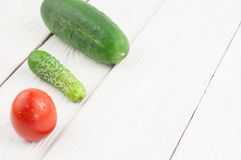 Red ripe tomato big and little fresh green cucumber on rustic planks. Red ripe tomato big and little fresh green cucumber on white rustic planks royalty free stock photo