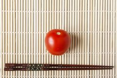 Red ripe tomato and chopsticks on bamboo mat closeup. Natural vegetables for dietary and healthy food. Chinese or japanese kitchen. Concept. Top view. Copy Royalty Free Stock Photo