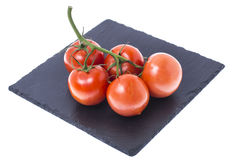 Red ripe tomatoes on black stone. Studio photo Royalty Free Stock Images