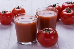 Red ripe tomatoes. With glass of tomato juice on white background Royalty Free Stock Images