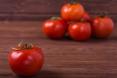 Red ripe tomatoes. The group of ripe tomatoes on wooden background Stock Image
