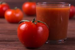 Red ripe tomatoes. With glass of tomato juice on wooden background Stock Images